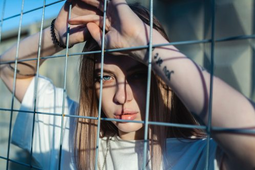 photo-of-woman-leaning-on-screen-fence-2926249