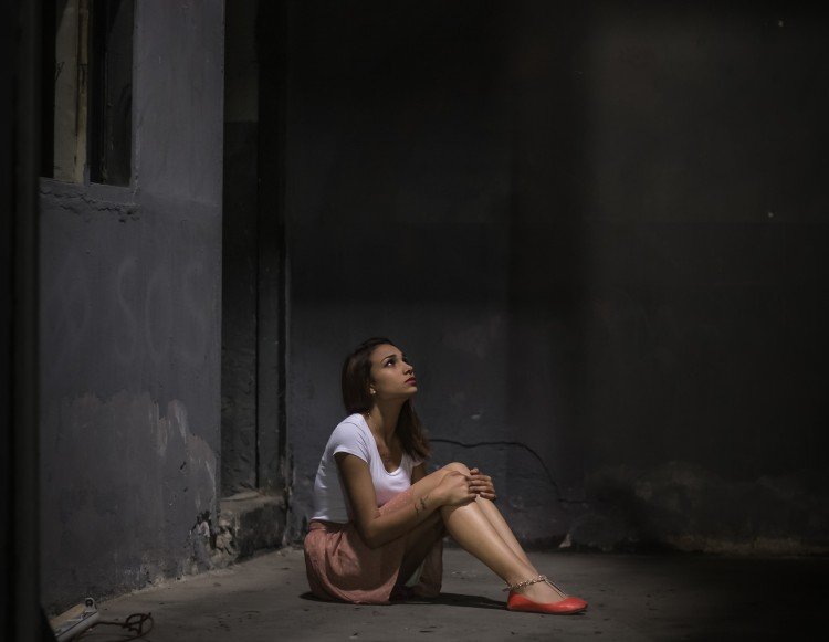 Young woman locked alone in a dungeon looking up to a window