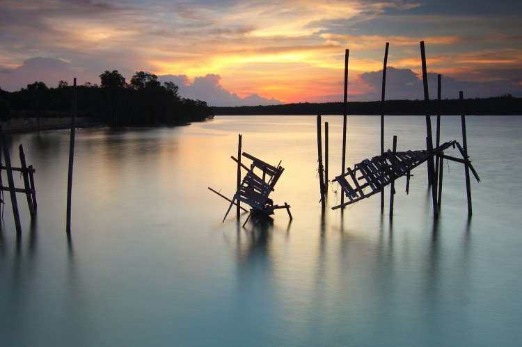 An old wooden bridge collapsed in a river at sunset
