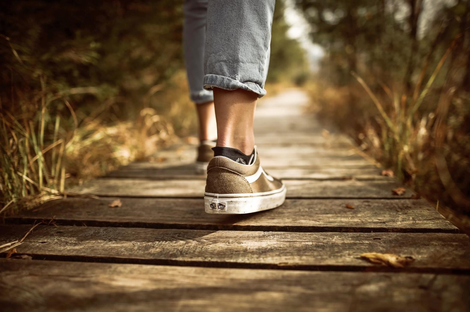 View of a woman's tennis shoes walking down a boardwalk