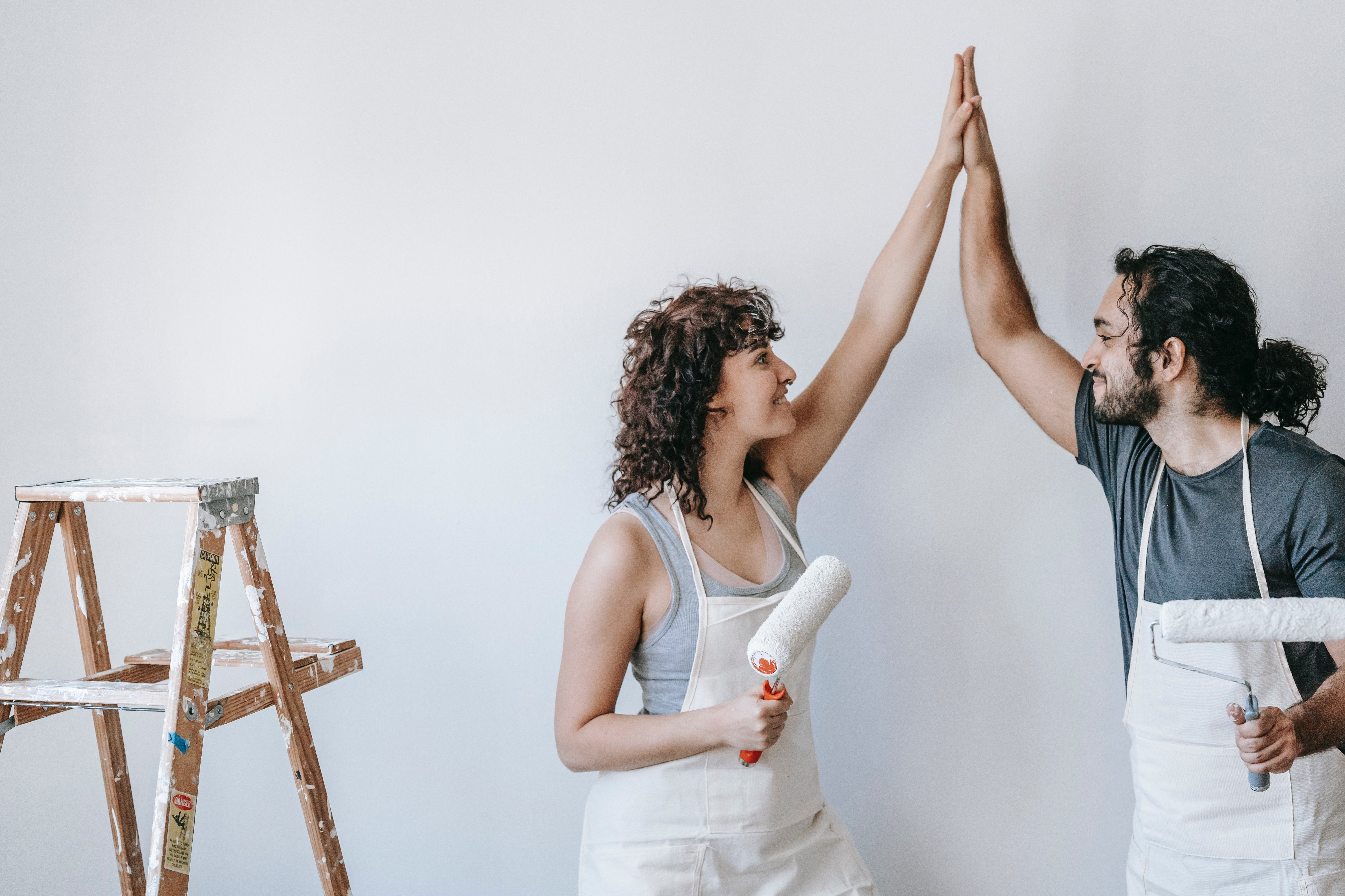 Two people high five after repainting a wall