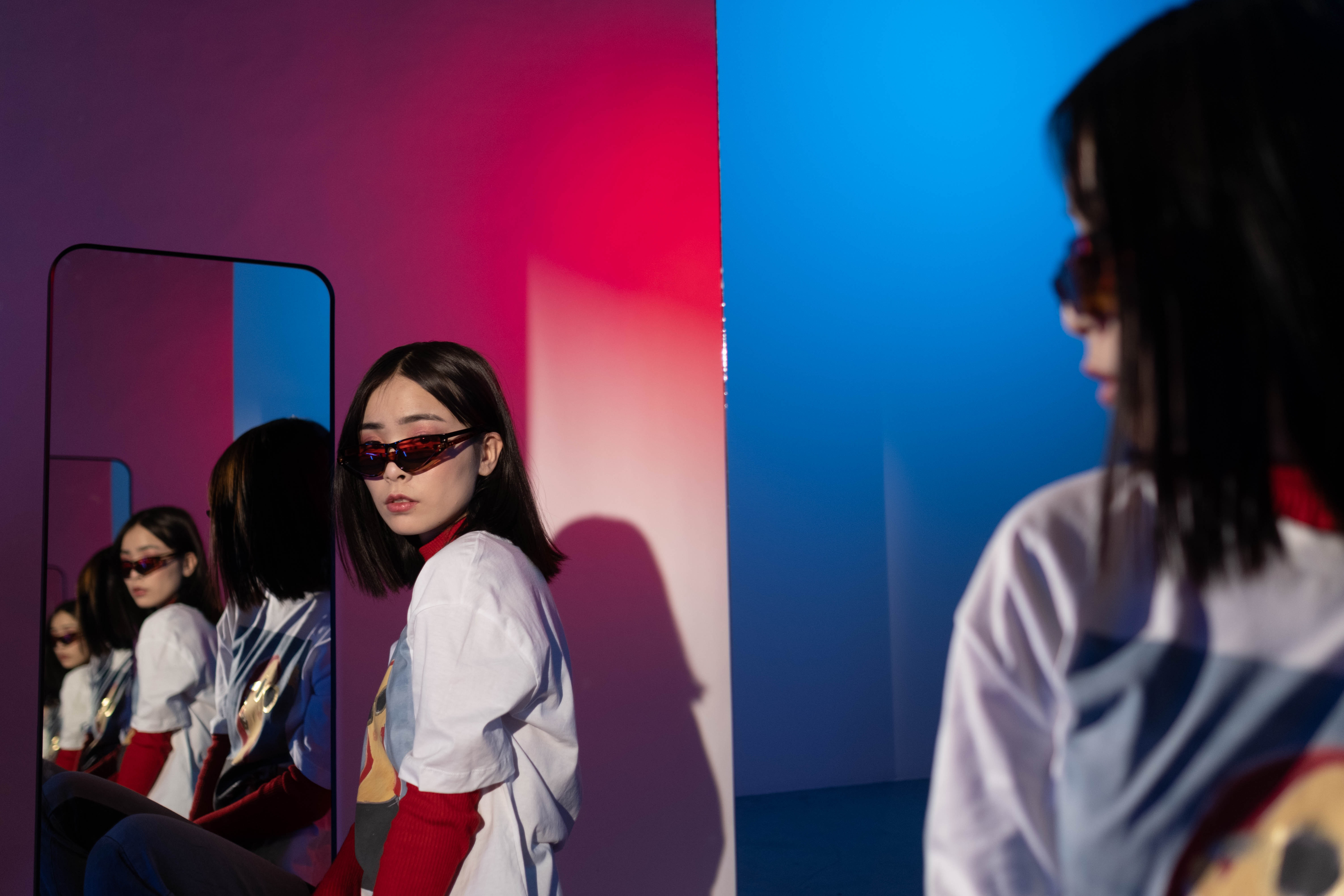 Woman in sunglasses between two mirrors, looking at the many reflections of herself
