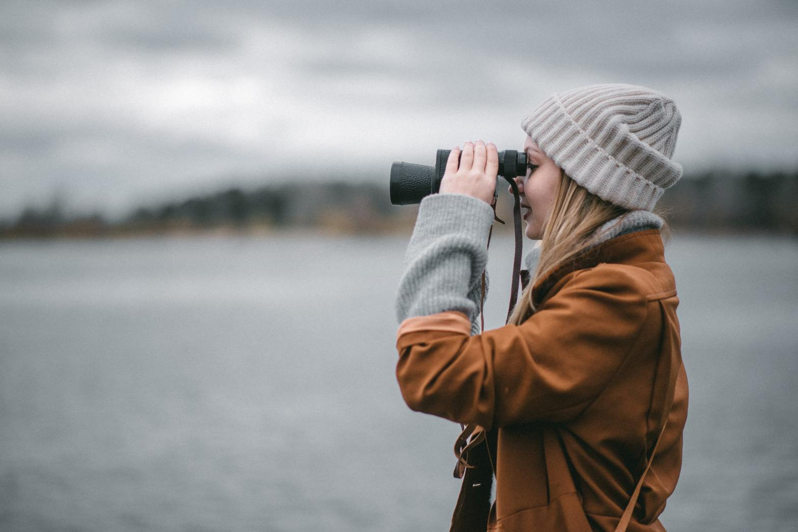 Woman looking through binoculars while standing beside water on a cloudy day