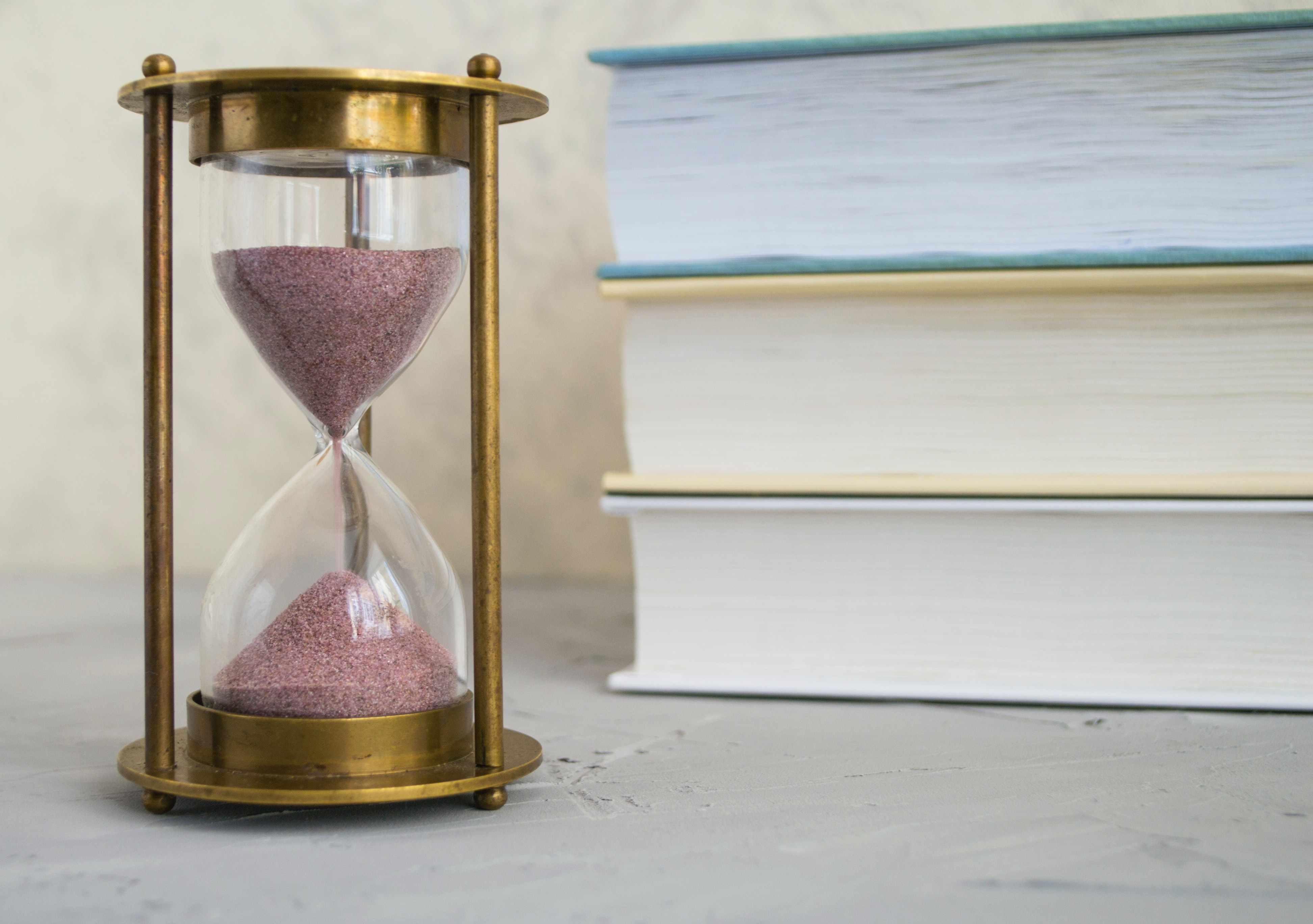 An hourglass drains beside a stack of books