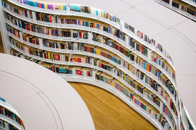 Curved white bookshelves in a library filled with colorful books