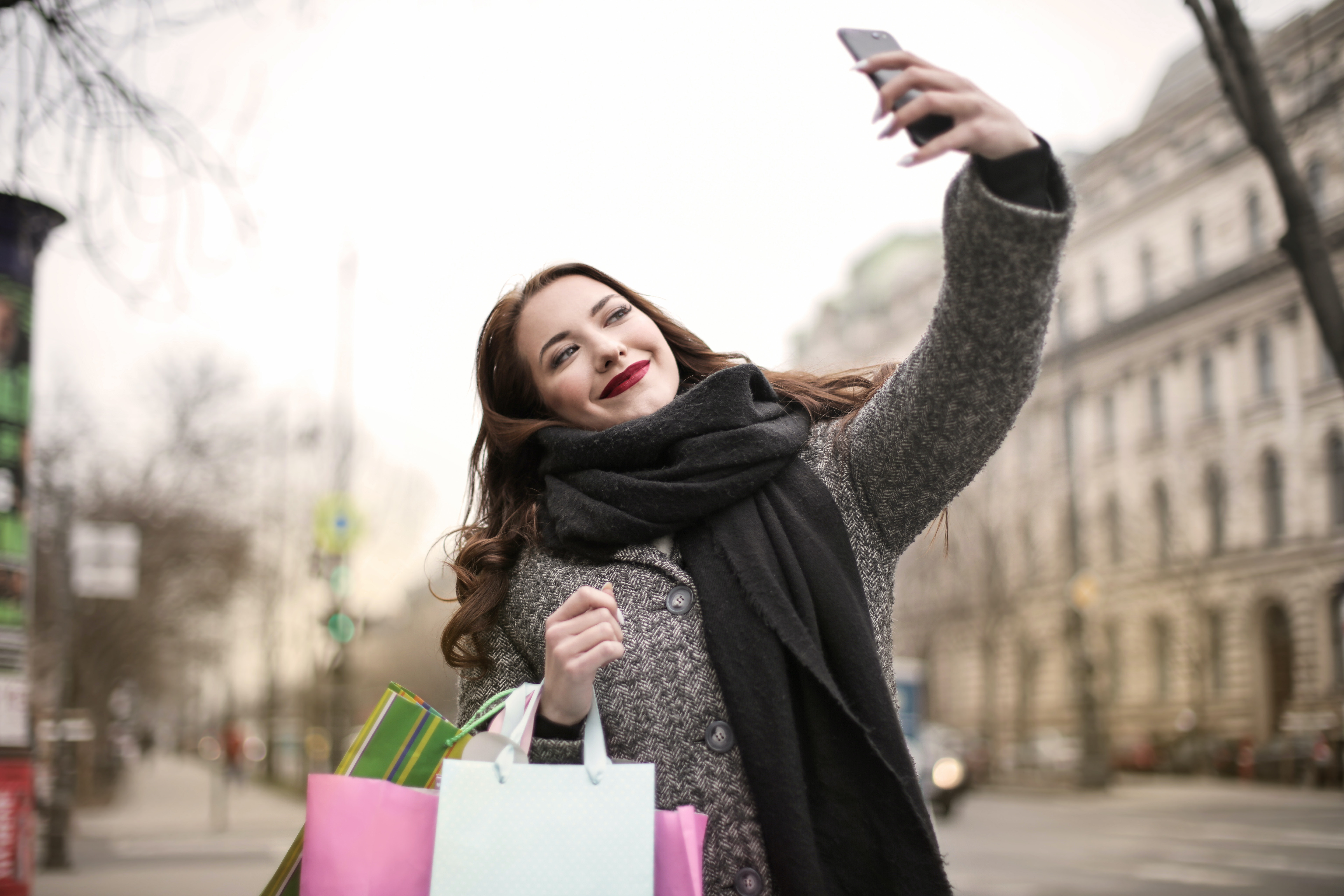 Millennial white woman taking a selfie while carrying expensive shopping bags