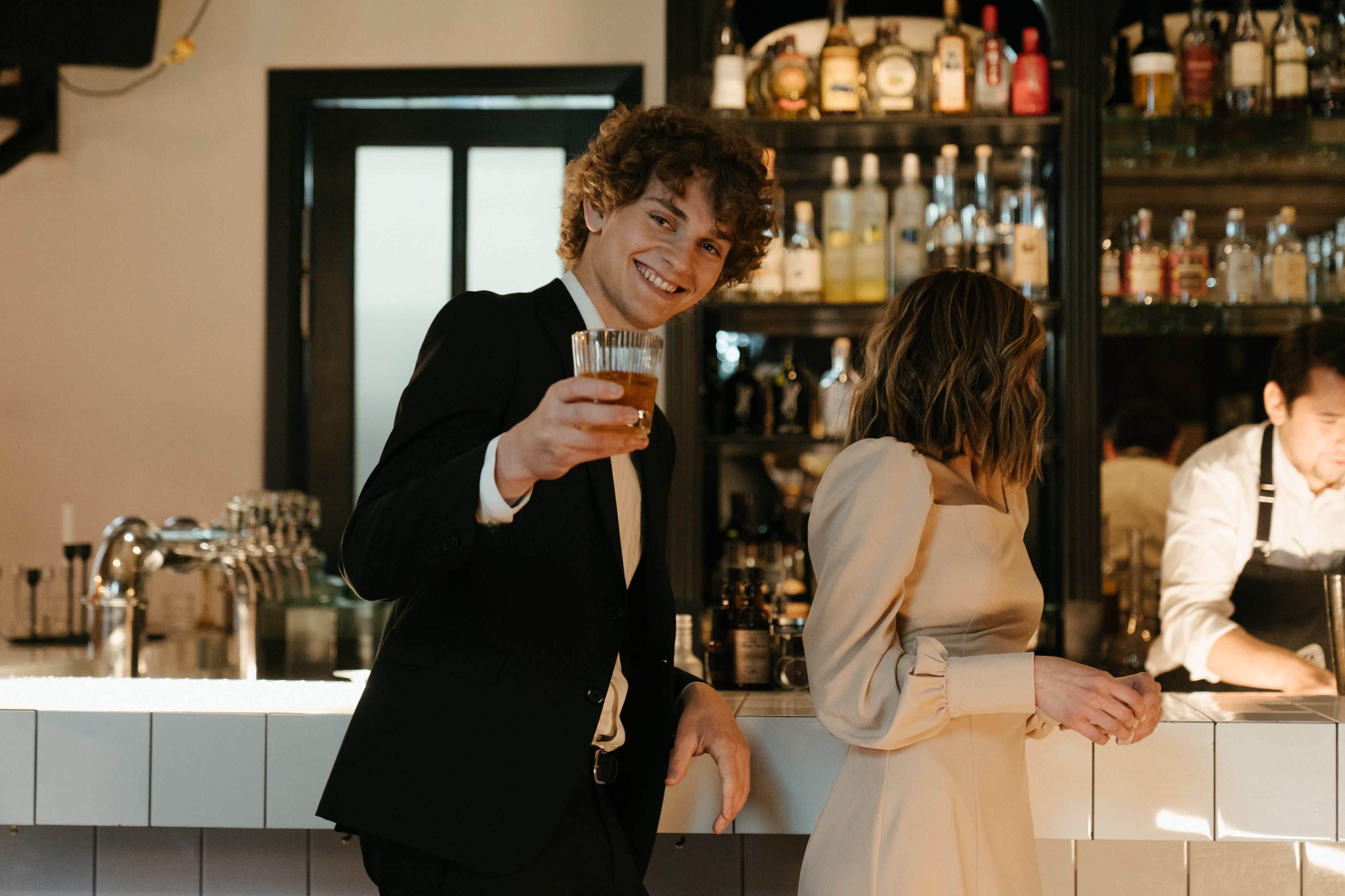 Young man in a bar grinning at the camera while holding a glass of beer