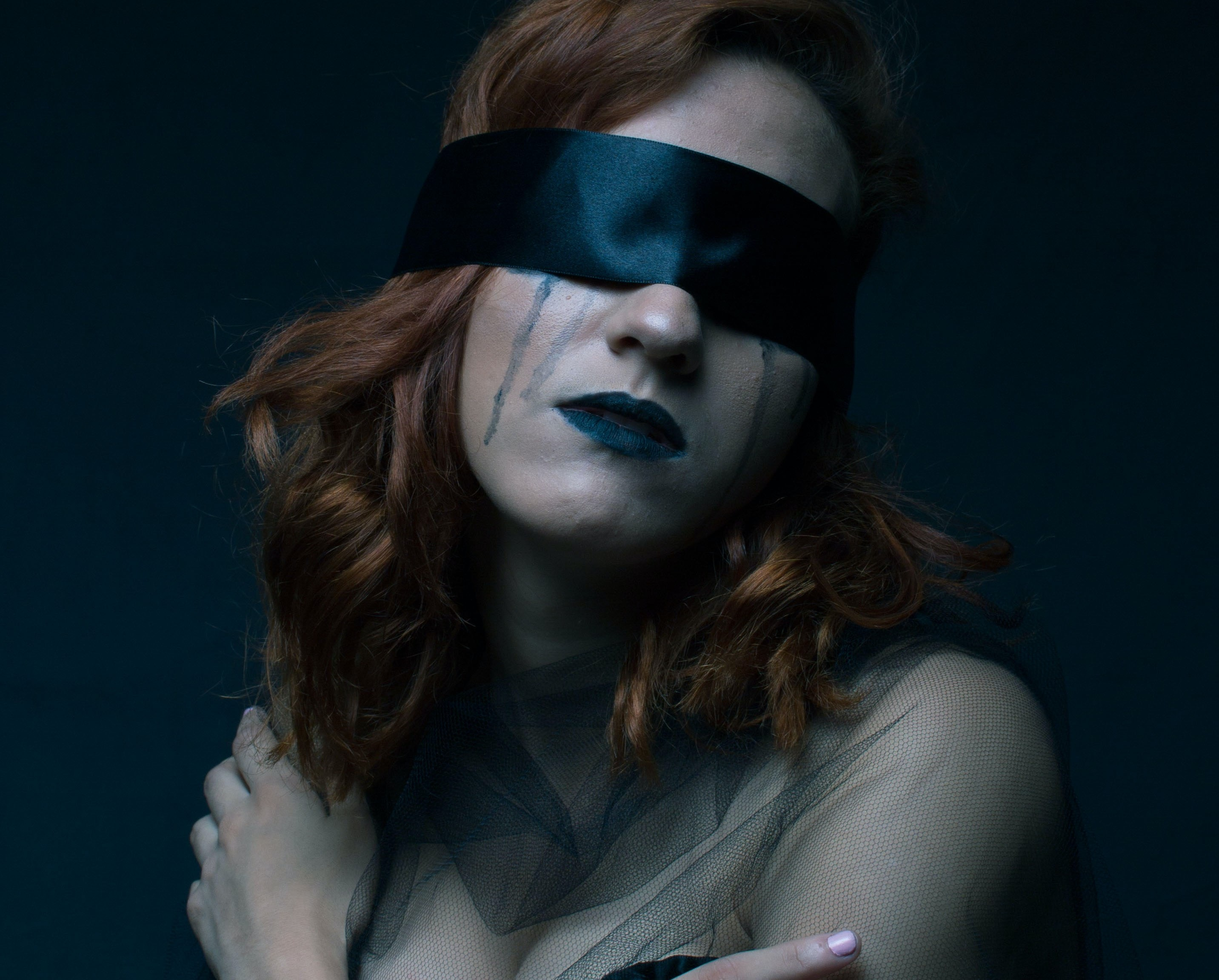 Blindfolded woman crying with mascara running while wearing lingerie
