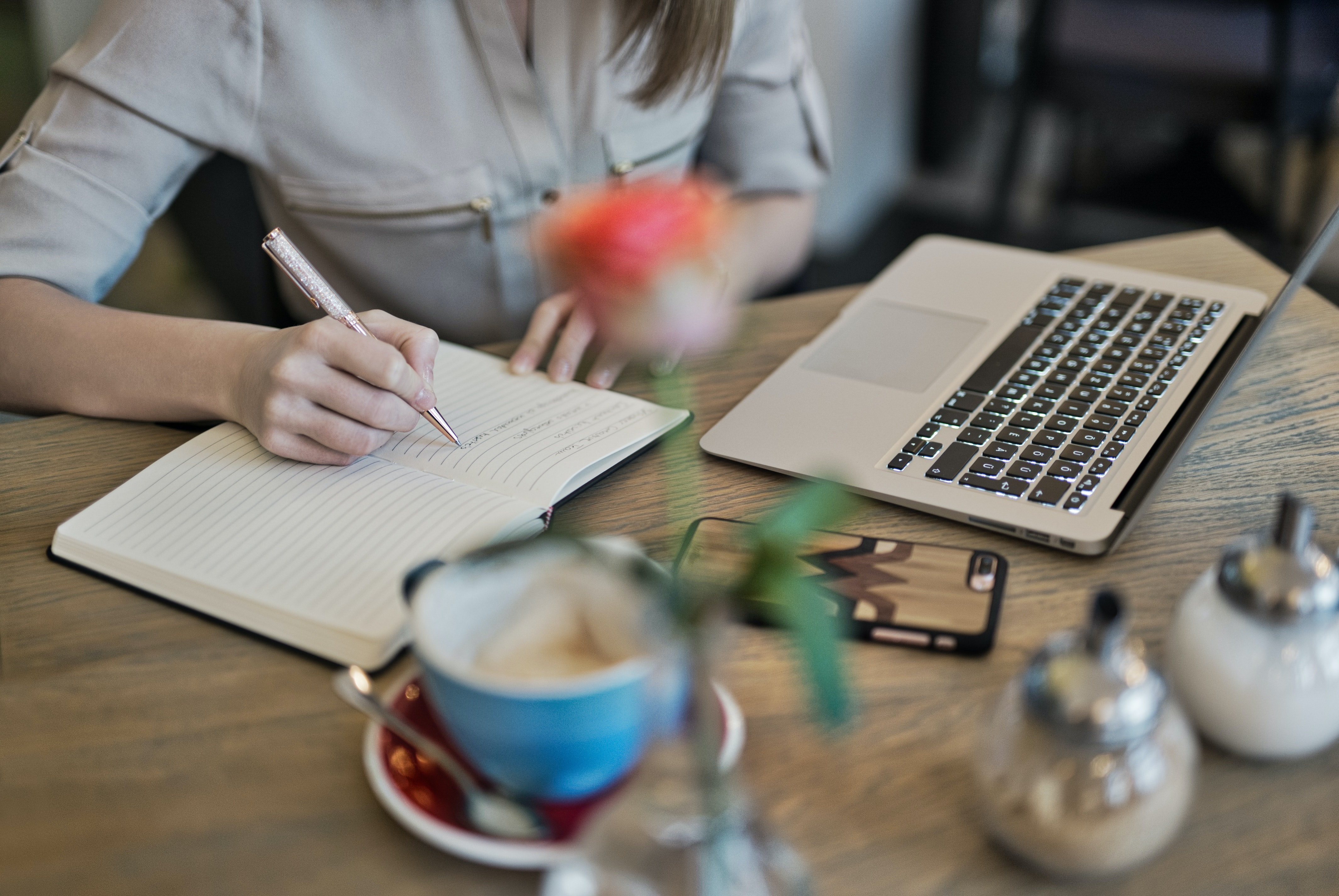 Woman writing in journal with laptop and coffee on the table