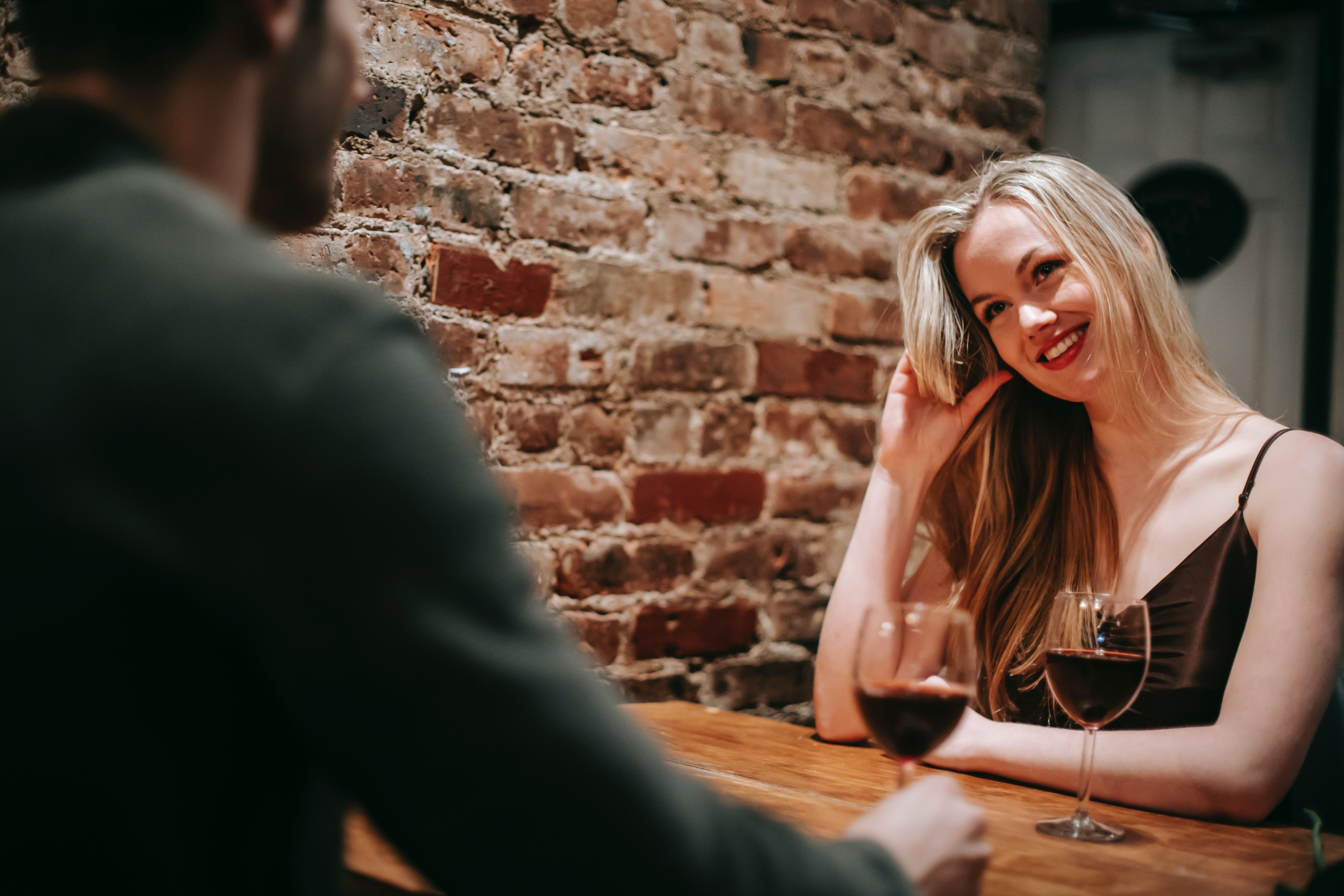 Woman drinking wine with a man while playing with her hair and smiling at him