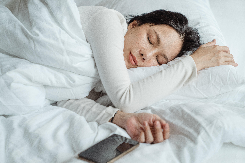 Woman sleeping peacefully beside her phone
