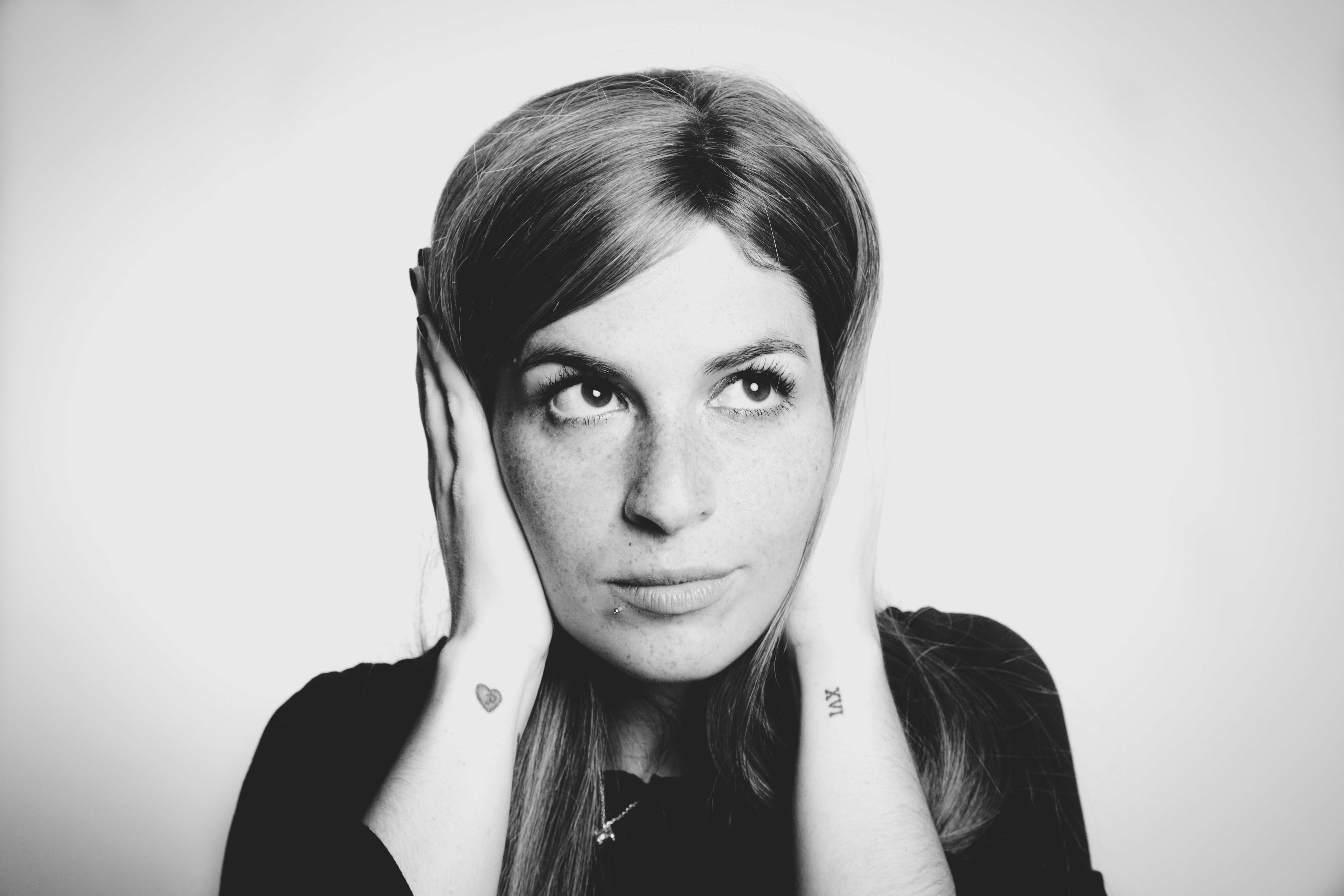 Woman covering her ears and looking away while pretending everything's fine