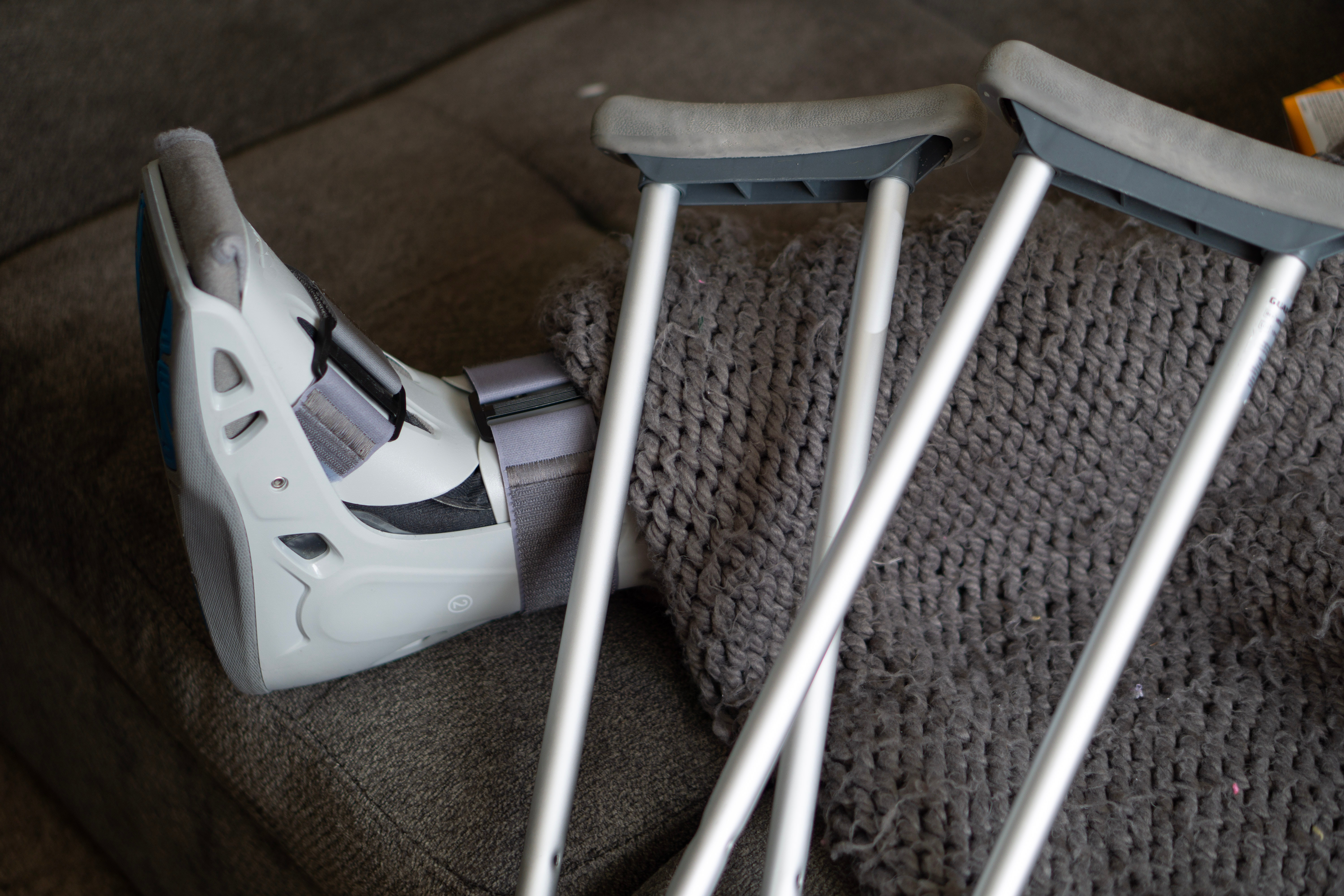 Patient with leg brace rests on a couch beside their crutches