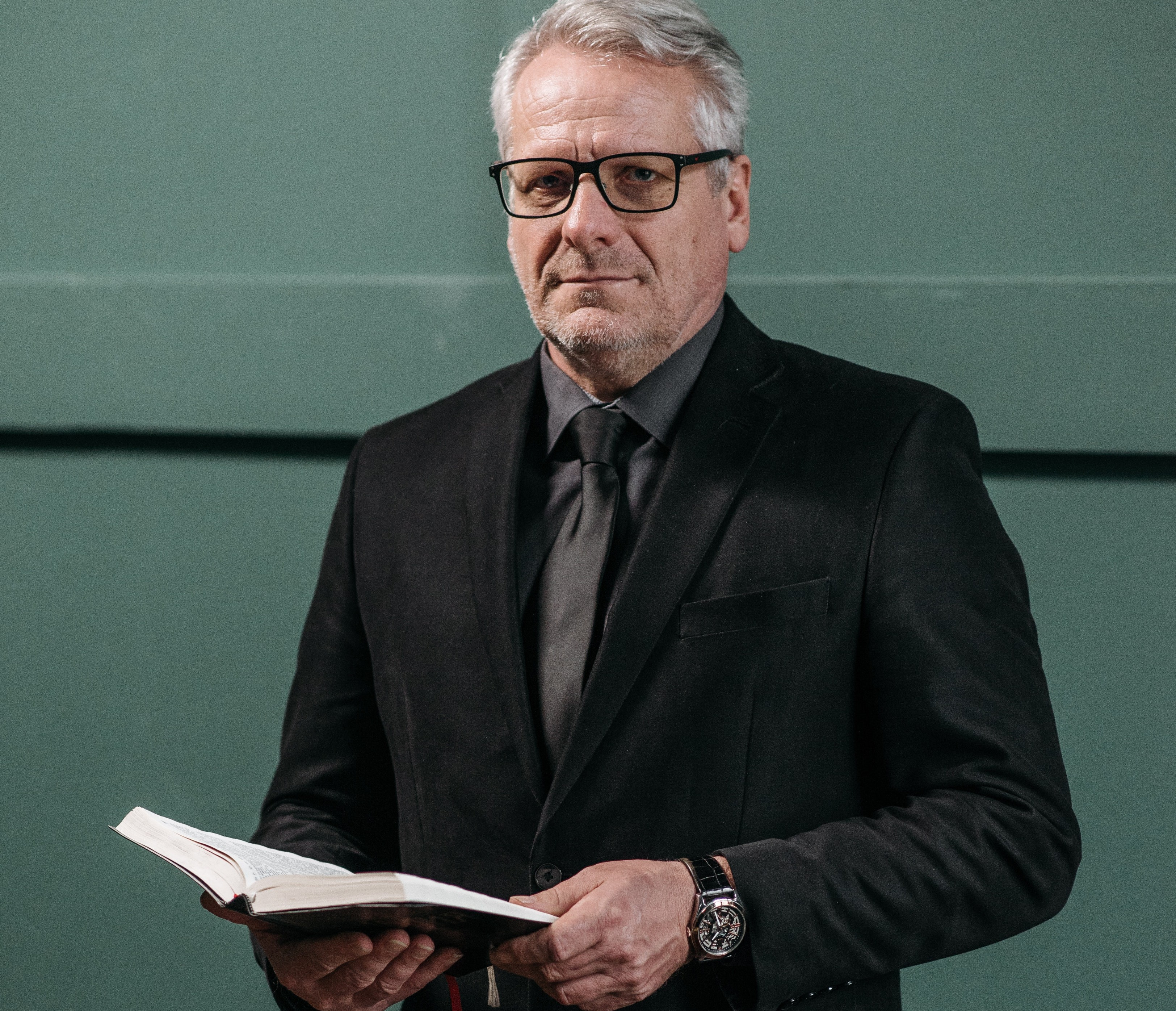 Professorial man with white hair holding an open book