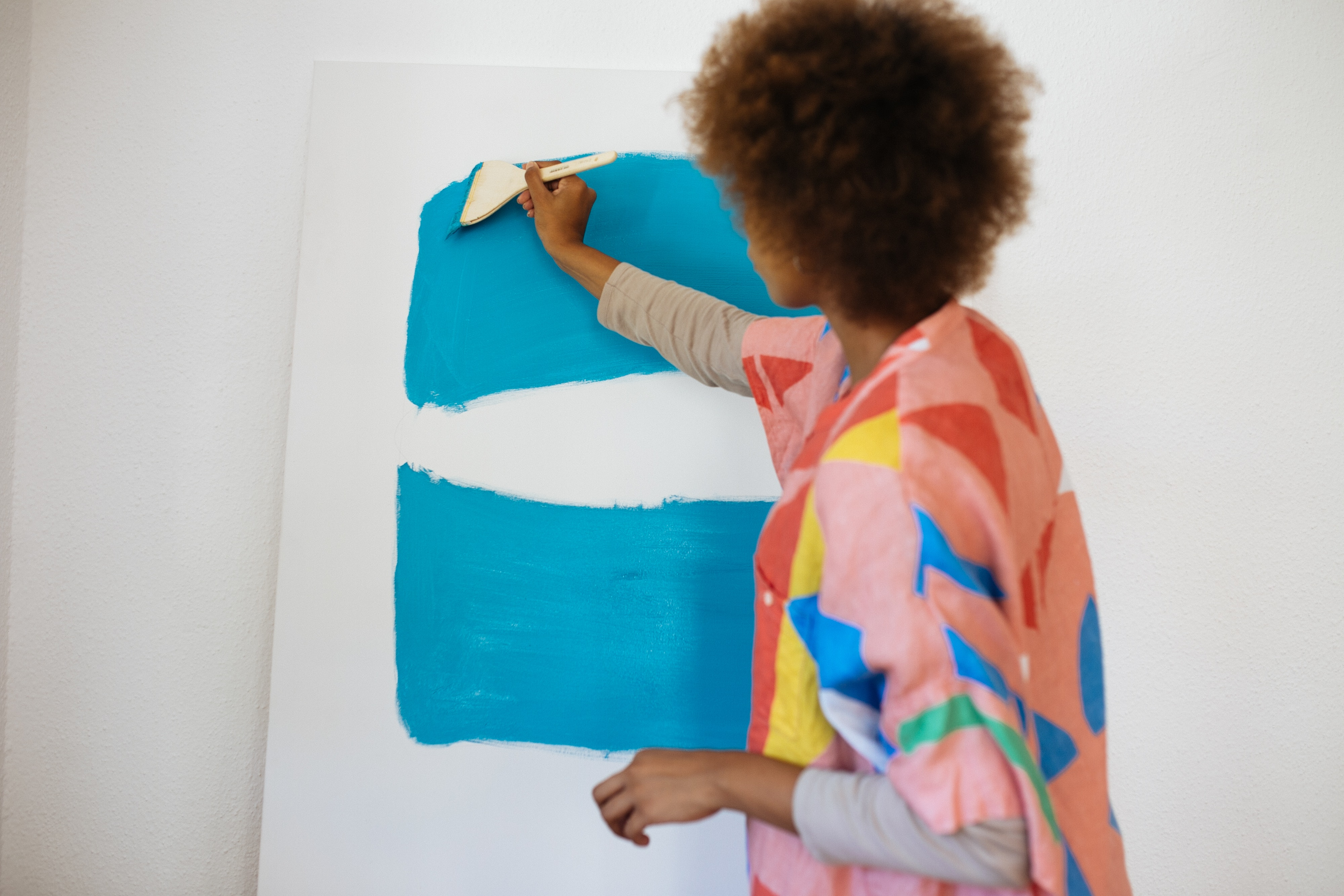 Black woman painting a white canvas with minimalist blocks of turquoise