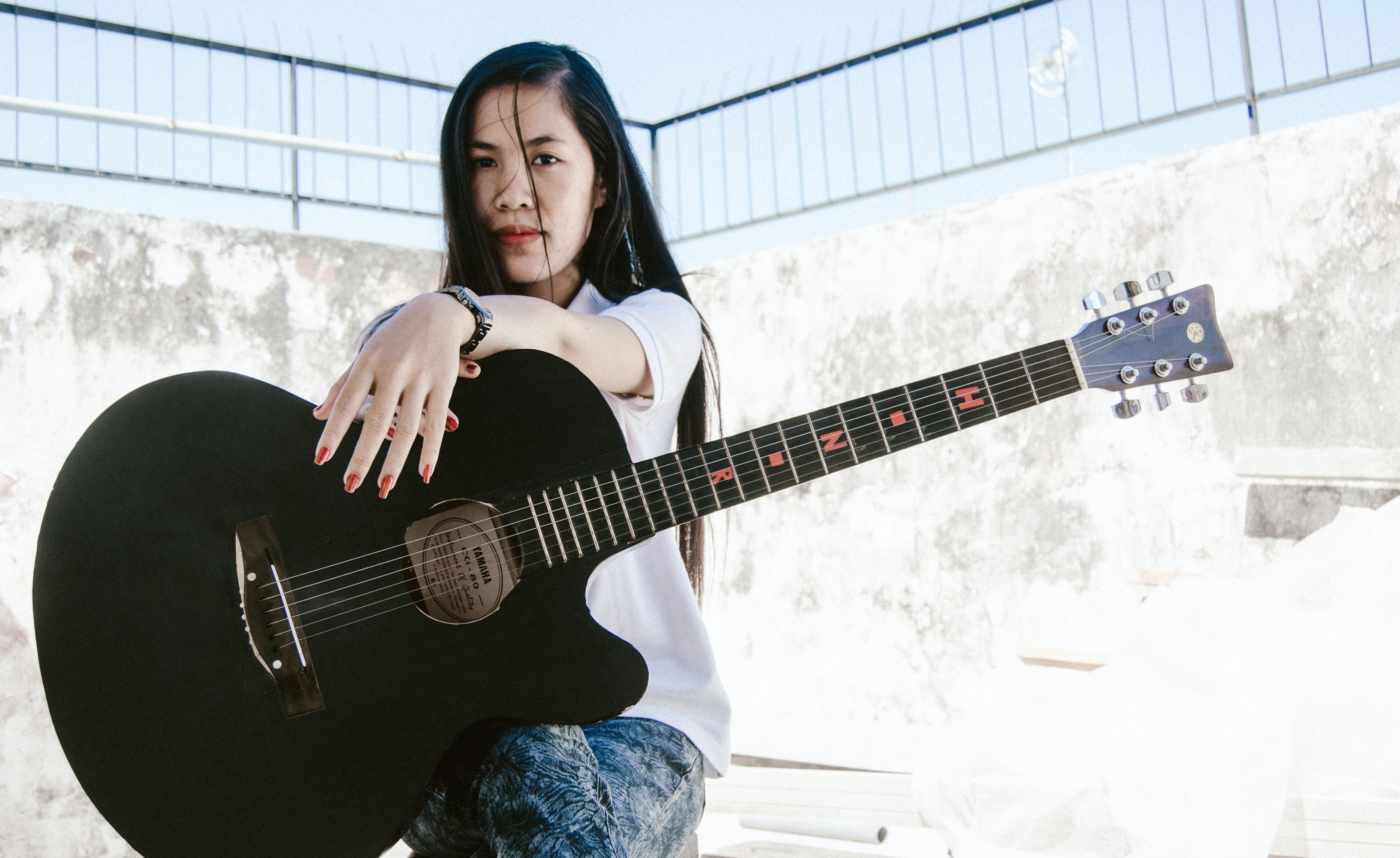 Indonesian woman with black folk guitar